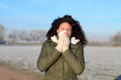 Young woman with flu blowing her nose Royalty Free Stock Image