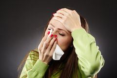 Young woman with flu. Woman with flu holding a tissue at her nose and her forehead, in pain Royalty Free Stock Photo