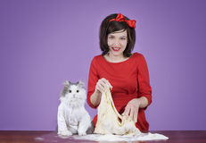 Young woman and a fluffy cat preparing dough Stock Image