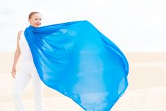 Young woman with flying blue scarf Royalty Free Stock Images