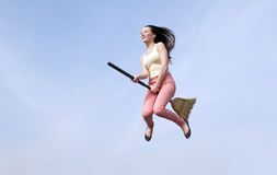 Young Woman flying broom. Happy young woman riding with a broom through the blue sky Stock Image