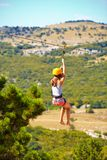 Young woman flying down on zipline in mountain, extreme sport Stock Images