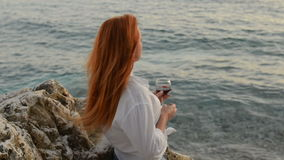 Young woman with flying hair standing with a glass of wine on the rocky beach of the Adriatic Sea. Young red-haired woman with flying hair sstanding with a glass stock footage