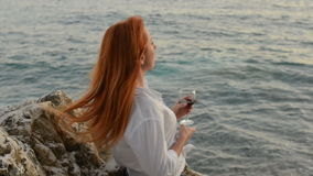 Young woman with flying hair standing with a glass of wine on the rocky beach of the Adriatic Sea. Young red-haired woman with flying hair sstanding with a glass stock video footage