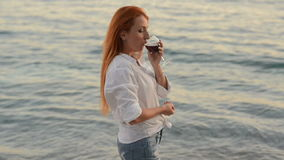 Young woman with flying hair standing with a glass of wine on the rocky beach of the Adriatic Sea. Young red-haired woman with flying hair sstanding with a glass stock video