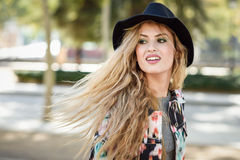 Young woman with flying hair wearing jacket and ha Royalty Free Stock Photo