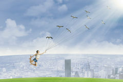 Young woman is flying by holding birds Stock Image