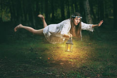 Young woman flying in the woods Royalty Free Stock Photo