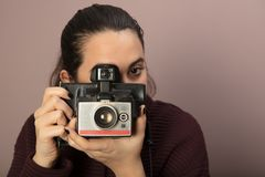Young woman focusing on the viewer. And taking picture with a vintage camera Stock Image