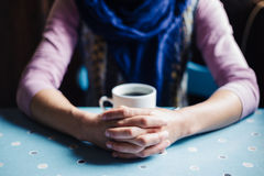 Young woman with folded hands and coffee Stock Images