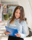 Young woman with folder. Young woman with blue folder in office royalty free stock images