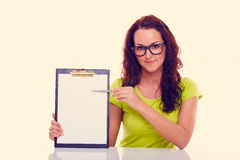 Young woman with folder. Toned. Young woman showing on the folder and sitting behind a desk. Toned Stock Images