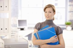 Young woman with folders in office. Portrait of young woman in office, holding file folders. Looking at camera, smiling Royalty Free Stock Photo
