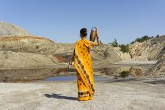 Woman goes for water. Young woman in a folk dress with a clay jar on her shoulder goes to a spring in an arid area royalty free stock images