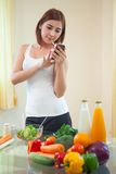 Young woman Following Recipe On mobile phone Royalty Free Stock Image