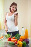 Young woman Following Recipe On mobile phone Stock Image