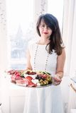 Young woman with food platter. Young woman holding a food platter in her hands and smiling royalty free stock photo
