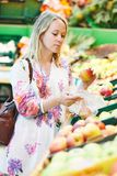 Young woman at food shopping in supermarket. Woman choosing bio food fruit apple in vegetable supermarket during shopping Stock Images