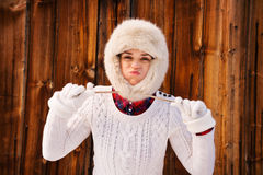 Young woman fooling around with furry hat near rustic wood wall Royalty Free Stock Image
