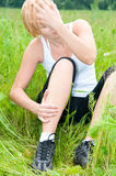 Young woman with a foot trauma. Young woman with foot trauma in  field Royalty Free Stock Images