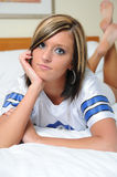 Young woman in football jersey laying on bed Royalty Free Stock Photos
