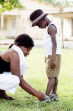Young woman footwear  her child. Squatting, this young women ties the laces of the shoe of his chil Royalty Free Stock Image
