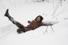 Young woman in the forest. Young woman is lie in the snow in the winter forest Royalty Free Stock Photos