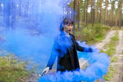 Young woman in forest having fun with blue smoke grenade, bomb.  Stock Photo