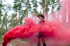 Young woman in forest having fun with red smoke grenade, bomb. Royalty Free Stock Photos