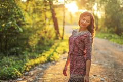 Young woman on forest path, looking down over her shoulder sun behind her, backlight creates nice bokeh in background.  stock photos