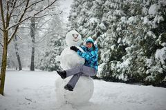 A young woman in the forest in winter hugs a big snowman royalty free stock images