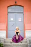 Young woman in formal gown. A young woman in a formal gown sitting on the stairs Royalty Free Stock Photography