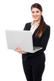 Young woman in formals posing with a laptop Royalty Free Stock Images