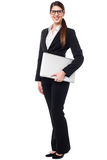 Young woman in formals posing with a laptop Royalty Free Stock Photos