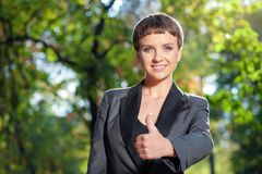 Young woman in formalwear showing her thumb up and smiling. Well done! Beautiful young caucasian woman in formalwear showing her thumb up and smiling while Royalty Free Stock Photos