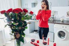 Young woman found bouquet of roses with candle, wine and gift box on kitchen. Happy excited girl. Valentines day stock images