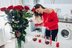Young woman found bouquet of roses with candles, wine and gift box on kitchen. Happy girl opens present. Valentines day royalty free stock images