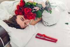 Young woman found bouquet of roses with jewellery in gift box in bed. Happy girl smelling flowers. Valentines day royalty free stock photography