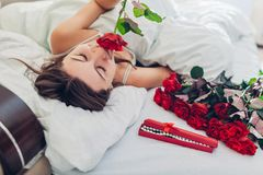 Young woman found bouquet of roses with jewellery in gift box in bed. Happy girl smelling flowers. Valentines day stock image