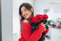 Young woman found bouquet of roses on kitchen. Happy girl holding and hugging flowers. Valentines day stock photography