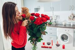 Young woman found red roses with candle, wine and gift box on kitchen. Happy girl smelling flowers with cat. Women`s day stock images