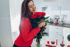 Young woman found red roses with candles, wine and gift box on kitchen. Happy girl holding flowers. Valentines day royalty free stock image