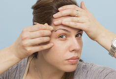 A young woman framing her eyebrows, close up Stock Photos