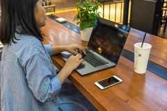 Young woman freelance working on laptop and mobile phone royalty free stock photography