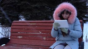 A young woman in a warm jacket uses a digital tablet in the park in the winter. A young woman freelancer in a gray warm coat sits on a bench and uses a digital stock video footage