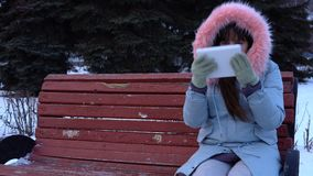 A young woman in a warm jacket uses a digital tablet in the park in the winter. A young woman freelancer in a gray warm coat sits on a bench and uses a digital stock video