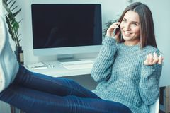 Young woman freelancer indoors home office concept casual style phone call stock photography