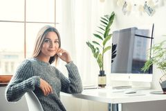 Young woman freelancer indoors home office concept casual style sitting smiling royalty free stock image