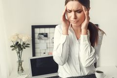 Young woman freelancer indoors home office concept formal style headache. Young female freelancer at home office formal feeling unwell headache Royalty Free Stock Image