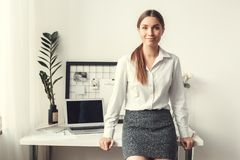 Young woman freelancer indoors home office concept formal style leaning on desk smiling. Young female freelancer at home office formal leaning on desk smiling stock photo